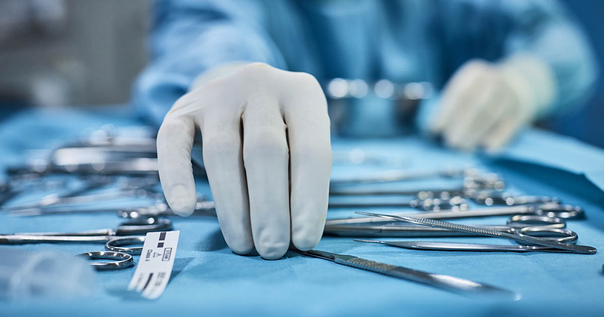 Surgeon picking up surgical tool from tray