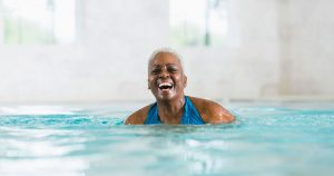 Older woman swimming in an indoor pool