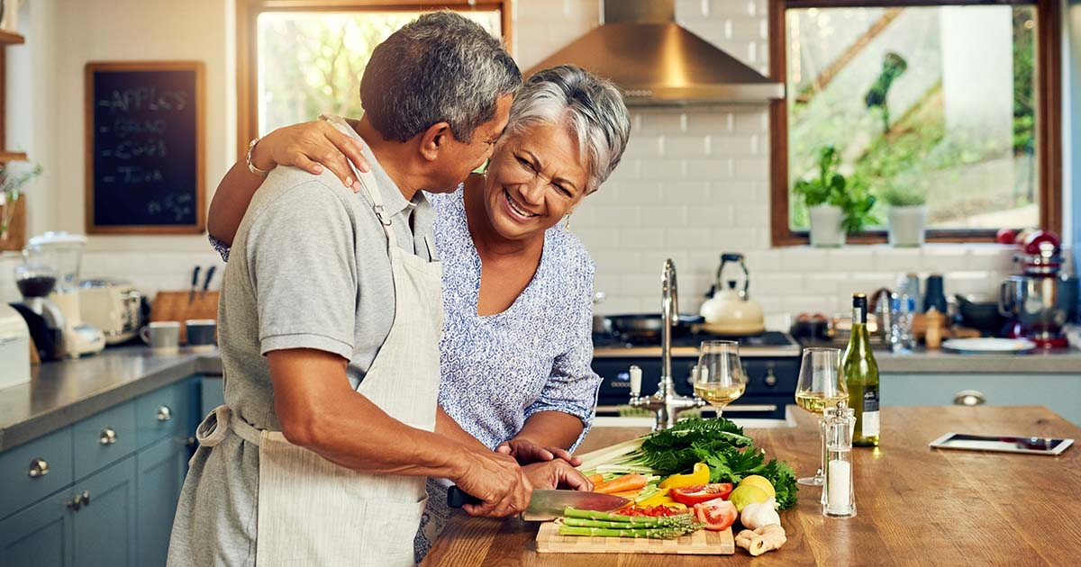 Happy mature couple cooking a meal together at home