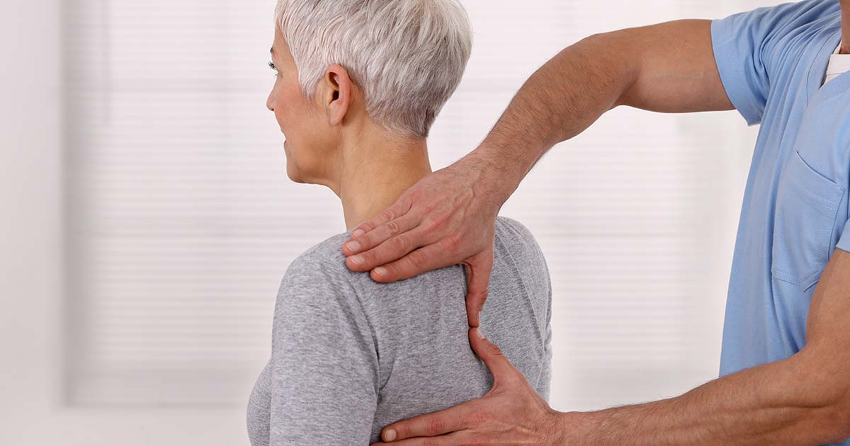 Mature woman having chiropractic back adjustment