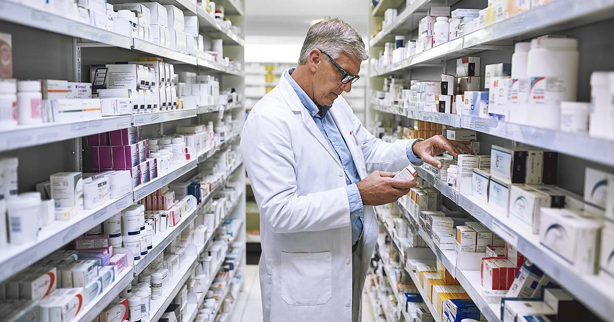 Pharmacist making notes of the medication stock on the shelves in a pharmacy