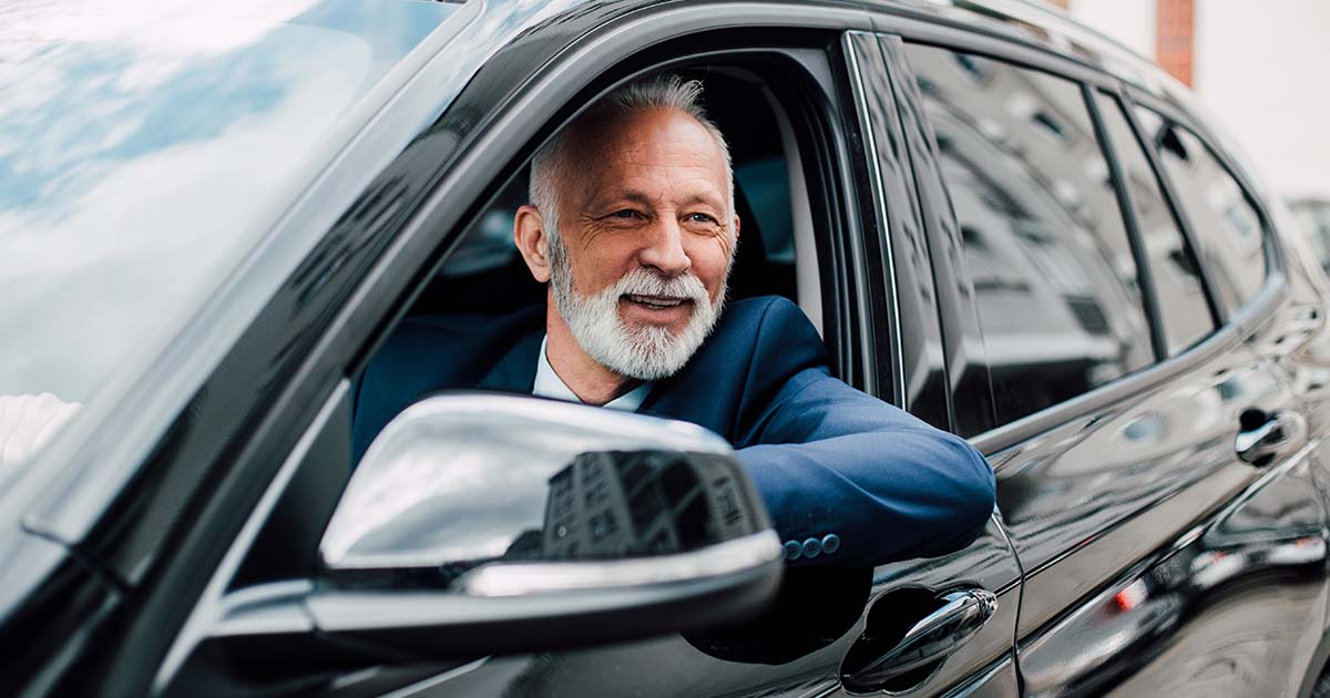 Mature man wearing business suit driving a car