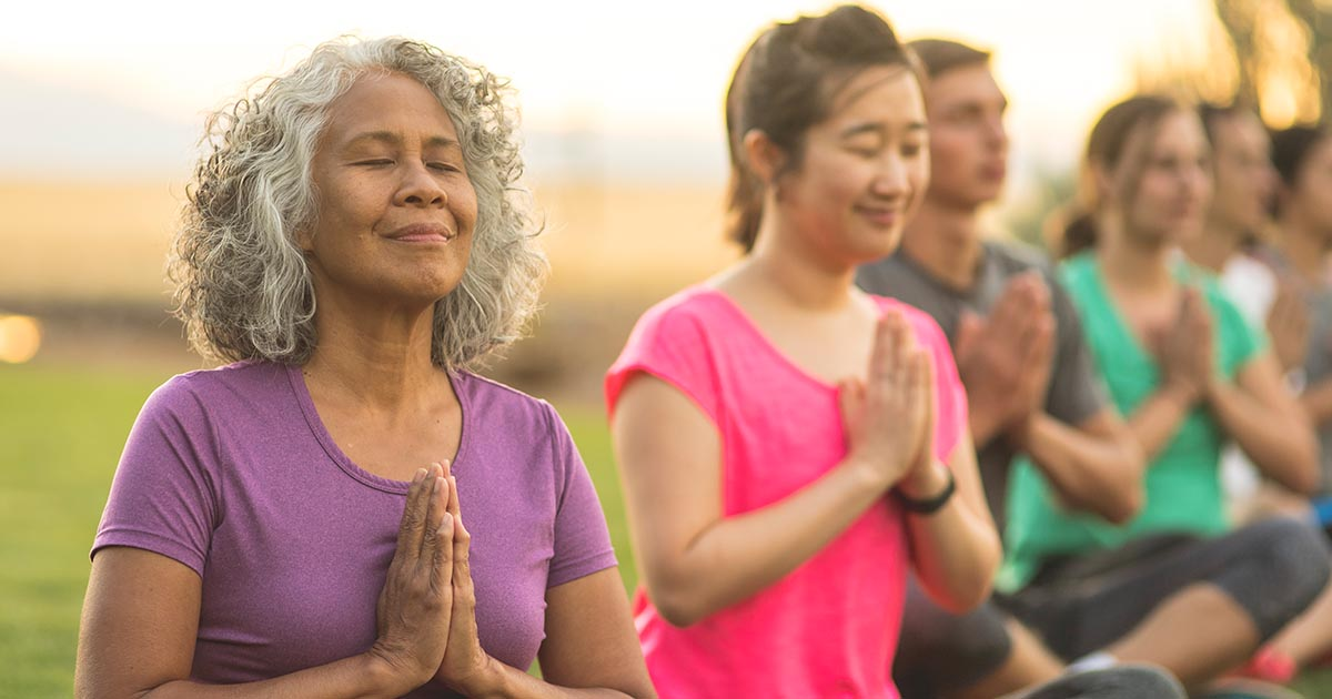 A senior woman meditates during a group yoga class