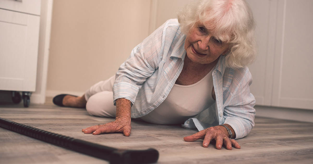 Senior woman on the floor at home and reaching for her cane
