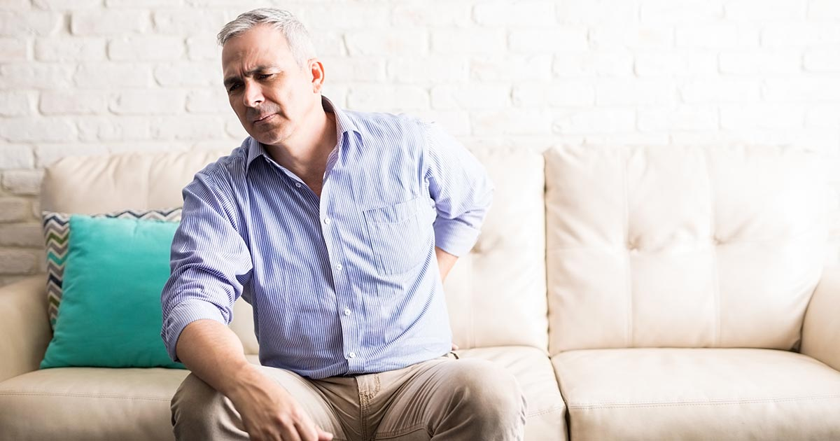 Man at home suffering from back pain