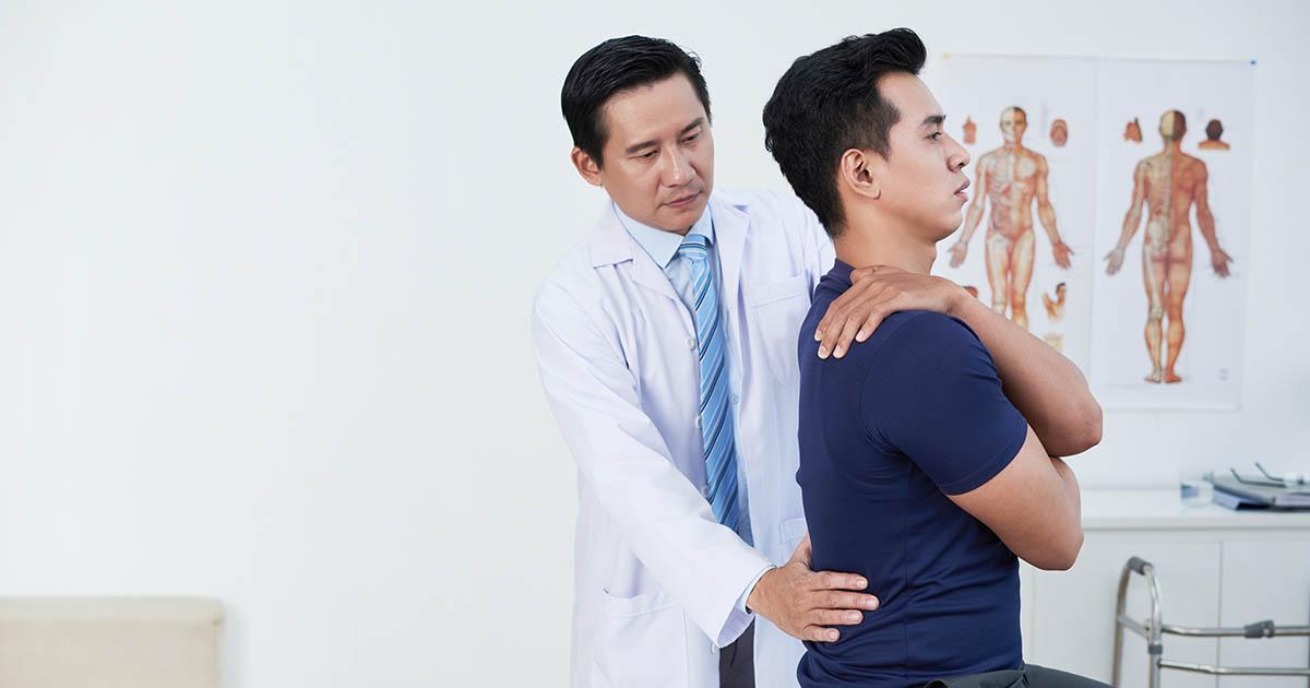 Doctor correcting patient's posture