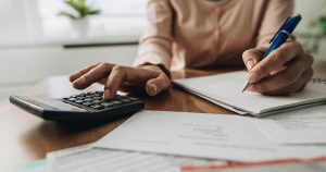 Woman planning budget and using calculator