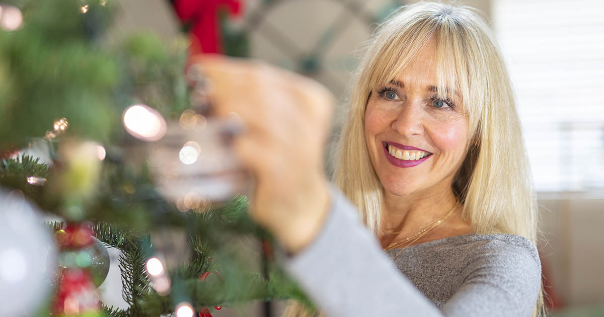 A smiling woman is decorating a Christmas tree in her apartment