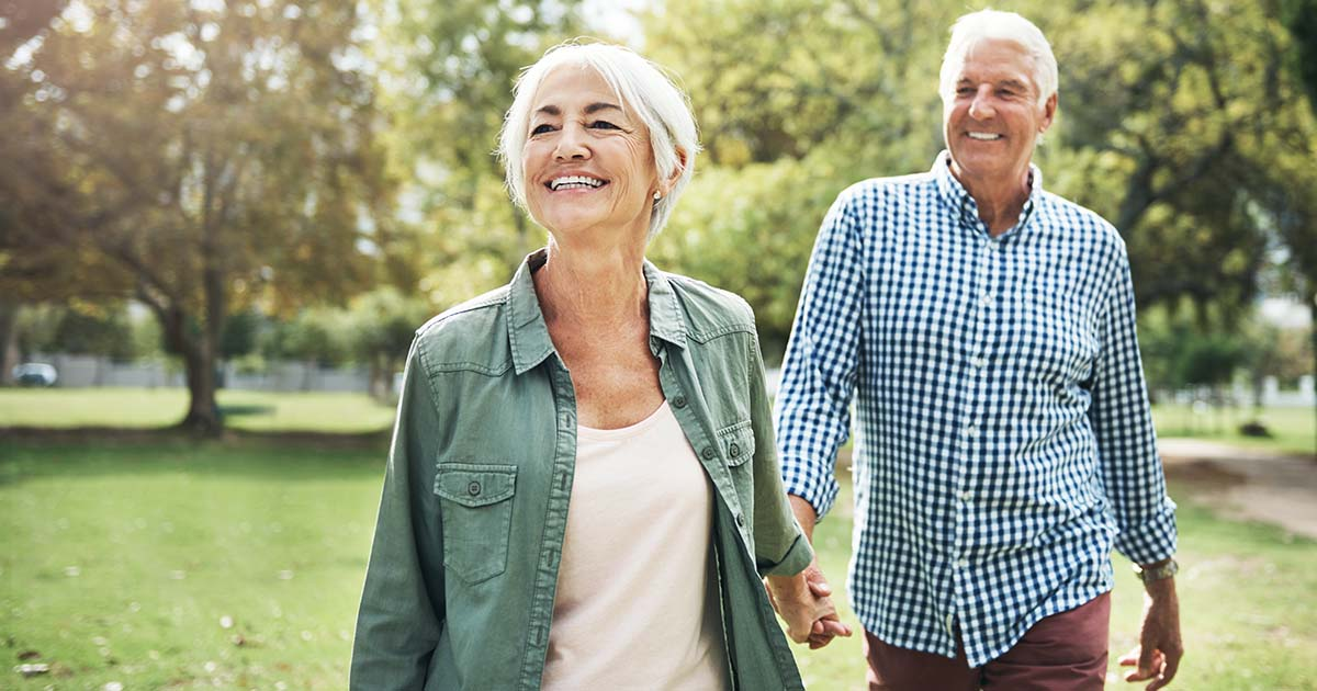 Happy senior couple going for a walk in the park