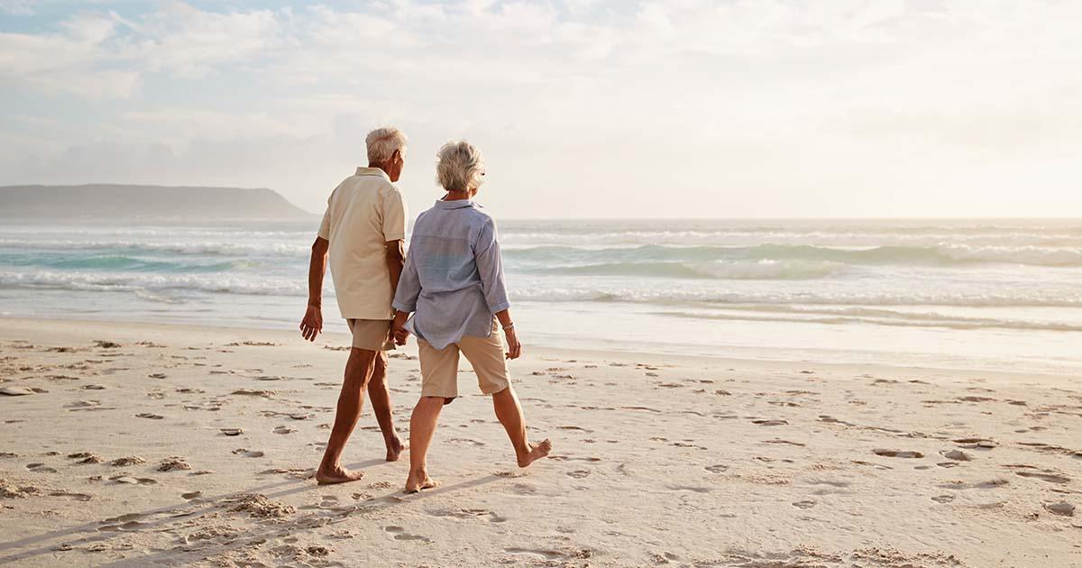 Couple walking along beach hand in hand