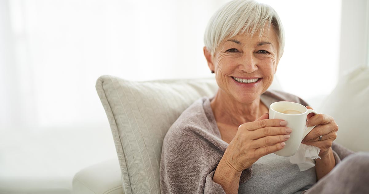Woman enjoying a relaxing coffee break on the sofa at home