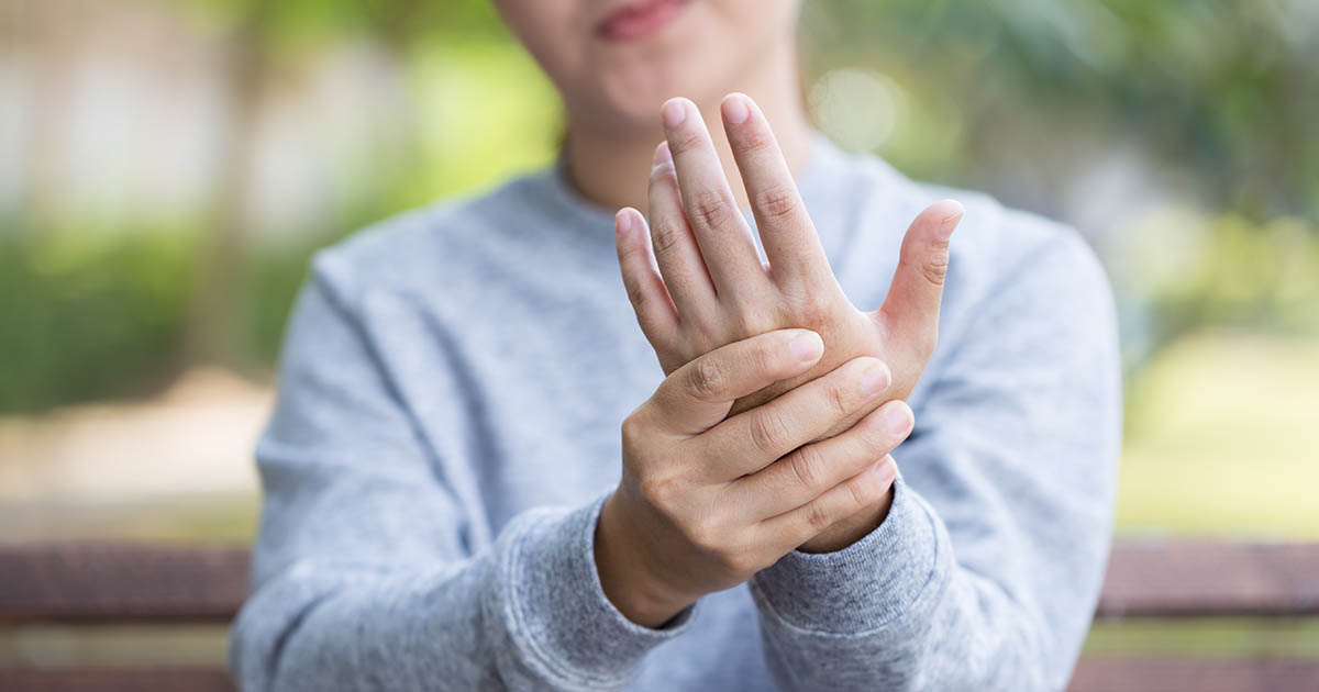 a woman (holding her hand up) who is experiencing osteoarthritis hand pain during the progression of osteoarthritis