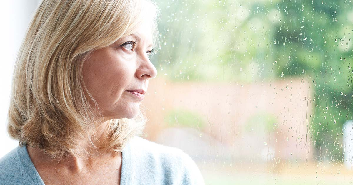 Woman looking out at rainy window