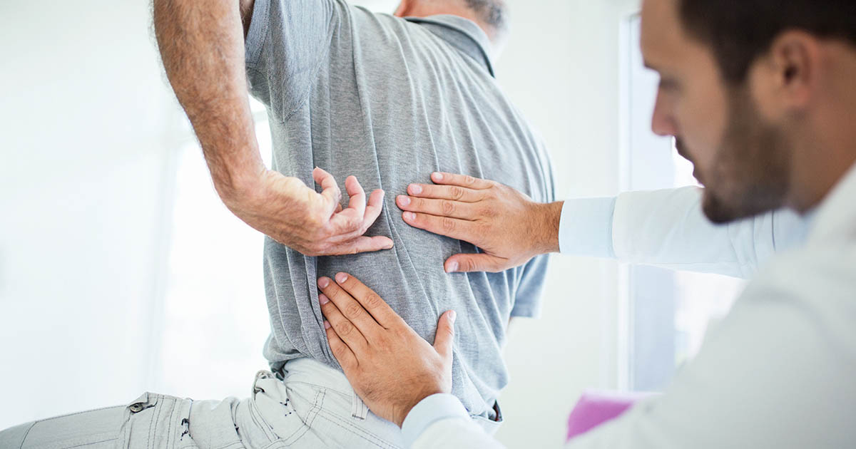 Doctor examining a male patient's back