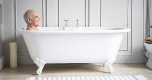 Older man soaking in a bathtub