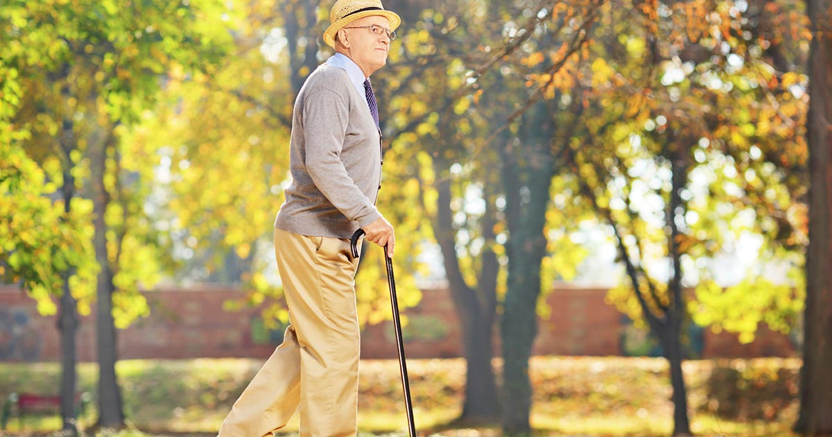 Older man with a cane walking in a park
