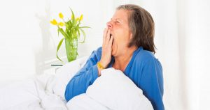 Woman sitting up in bed, yawning