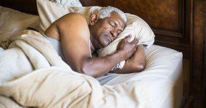 Older man sleeping in bed