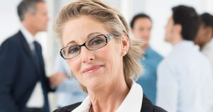 Older woman with coworkers in background