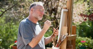 Older man painting on an easel outside