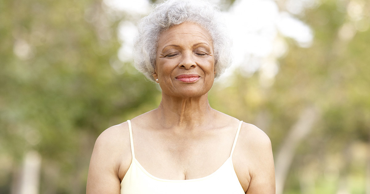 Older woman sitting outside with her eyes closed