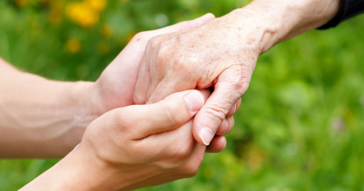 One person holding an older person's hand
