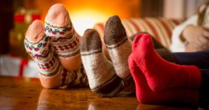 Three pairs of Christmas socks by the fireplace