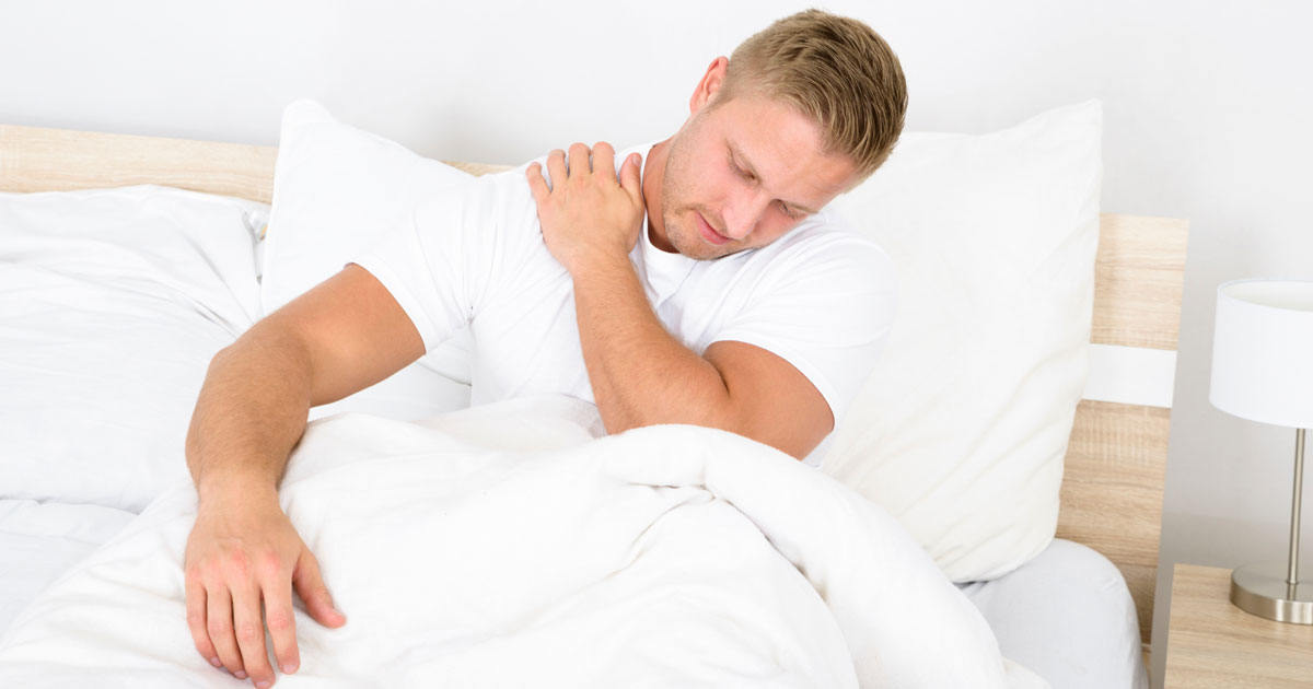 Man lying in bed holding his shoulder in pain