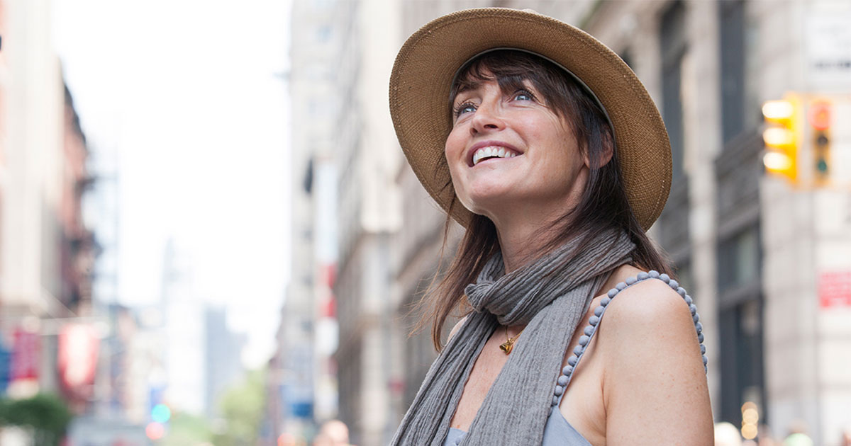 Woman wearing a sunhat outside smiling