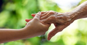 Younger person holding the hand of an older person