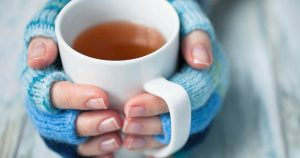 Woman wearing fingerless gloves holding a mug of tea