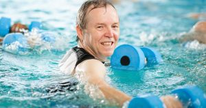 Man in swimming pool holding water weights