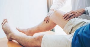 a doctor examining a patient with osteoarthritis of the knee