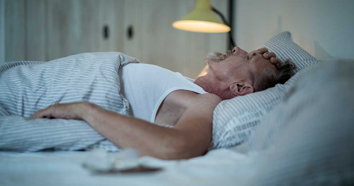 an elderly man being kept up at night by osteoarthritis pain