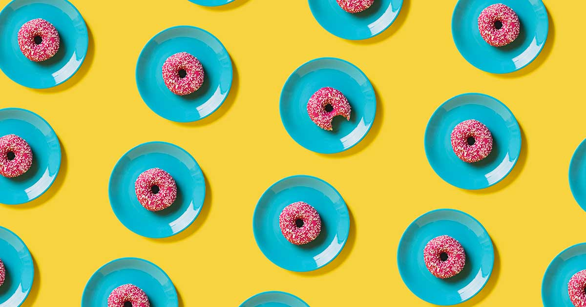 A pattern of pink donuts on blue plates, with a yellow background